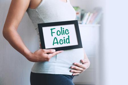 妊娠中の女性は、テキスト メッセージ - 葉酸のホワイト ボードを保持します。妊娠、親、準備、期待のコンセプトです。クローズ アップ, コピー