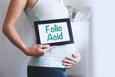 Pregnant woman holds whiteboard with text message - FOLIC ACID. Pregnancy, parenthood, preparation and expectation concept. Close-up, copy space, indoors.