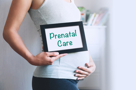Pregnant woman holds whiteboard with text message - Prenatal Care. Pregnancy, parenthood, preparation and expectation concept. Close-up, copy space, indoors. Stockfoto