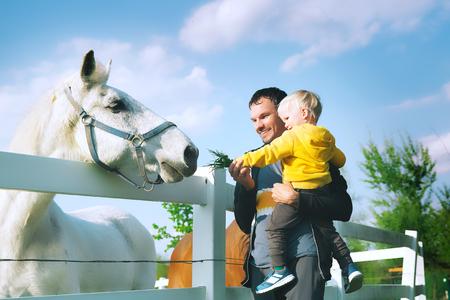 Le père et le fils nourrissent un cheval à la campagne. Famille dans une ferme au printemps. Enfant enfant jouant avec des animaux de compagnie à l'extérieur. Banque d'images - 77881050