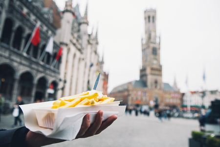 Tourist holds in hand popular street junk food - French Fries with mayonnaise on the background of city tourist streets of Bruges Belgium.