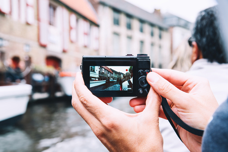 Tourists hands holding digital photo camera on vacations, taking picture of canal in Bruges, Belgium. View on city from boat. Travel Europe. Belgian traditional blurred architectural background