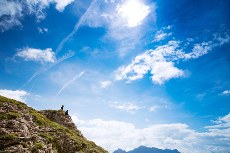 Couple of travelers (hikers) on top of a mountain enjoying valley view. Mangart is a mountain in the Julian Alps, located between Italy and Slovenia. Travel, Holidays, Freedom and Lifestyle Concept Stock Photo