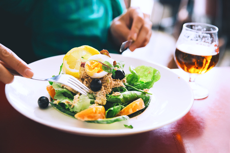 Classic Nicoise Salad or Tuna Salad and glass of Draft Beer. Dinner at restaurant.  People eating on the background. Food in Amsterdam, Netherlands, Europe. 스톡 콘텐츠