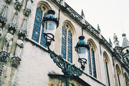Details of a historic building in Bruges, Belgium, Europe. Belgian traditional architecture. Close-up of lamp with blurred architectural background.