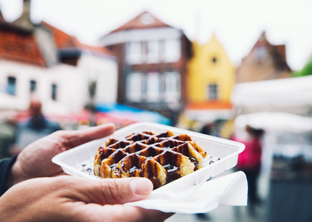 Tourist holds in hand popular street food - Belgium tasty waffle with chocolate sauce on the background of city tourist streets of Bruges, Belgium, Europe. Traditional Belgian dessert, pastry.