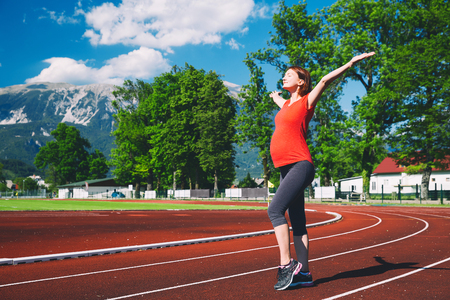 Happy pregnant sporty fitness woman with raised hands on red running track in stadium. Training, stretching at summer outdoors on running track line. Sport, healthy lifestyle while pregnancy concept.
