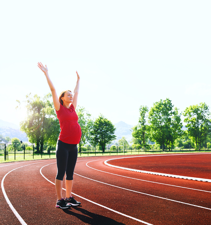 スタジアムの赤いトラックに上げられた手と幸せ妊娠スポーティなフィットネス女性。トレーニング、ランニング トラック ラインの屋外夏のストレ