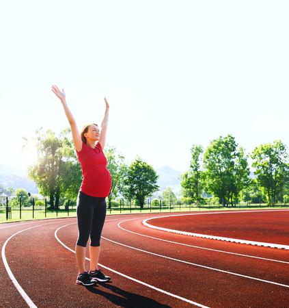 Gelukkige zwangere sportieve fitness vrouw met opgeheven handen op rode lopende track in het stadion. Opleiding, die zich uitstrekt in de zomer buitenshuis op de spoorlijn. Sport, gezonde levensstijl tijdens zwangerschapskoncept. Stockfoto