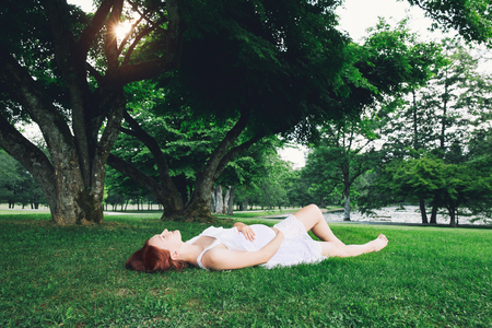 Beautiful pregnant woman in white dress on nature, outdoors. Expectant mother holds hands on belly on natural background of green grass in park at summer. Pregnancy, expectation, new life concepts.