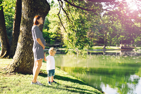 Pregnant woman with child outdoors. Mother and son on nature in summer park. Little child boy walking with mother, who pregnant for second time. Pregnancy, new life, family, parenthood concept. Banco de Imagens