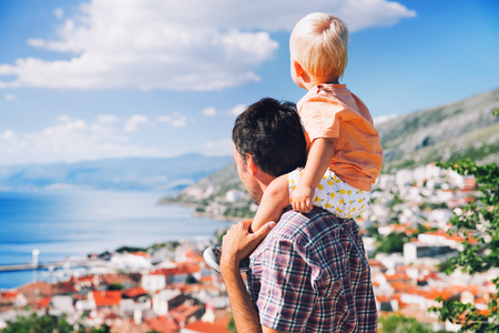Father and son on backgrounds of the coast and the Croatian village. Little child is sitting on fathers shoulders and looking on landscape of the sea at summer. Family, Vacation and Travel concept.