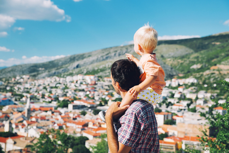 dalmatia: Father and son on backgrounds of the coast and the Croatian village. Little child is sitting on fathers shoulders and looking on landscape of the sea at summer. Family, Vacation and Travel concept.
