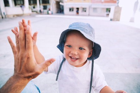 Cute boy son giving high five to father. Happy smiling portrait of child, outside. Close-up of adorable kid enjoying summer vacation. Family, Childhood, Parenthood and People concept.