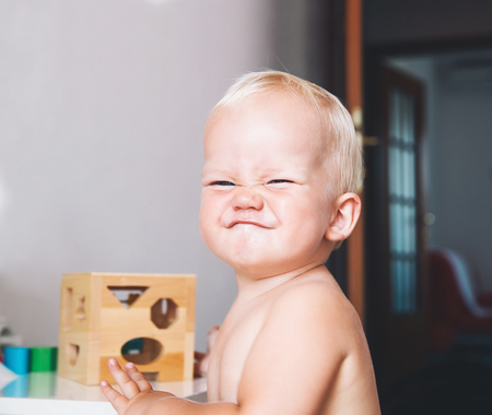 Cute toddler frowns and expresses disagreement on his face. Adorable baby boy makes a funny serious disagrees displeased face at home interiors. Portrait of an angry child. Early development of baby