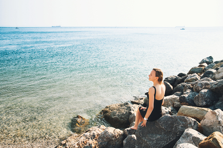 Slim young model girl in black dress on the background of sea or mountain lake. Beautiful woman relaxed and enjoyed over the sea sitting on the big wild stone beach, back view. Travel and Inspiration