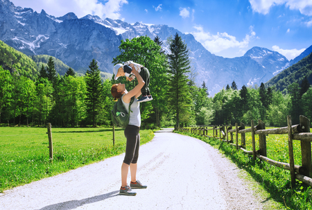 Logar valley or Logarska dolina, Slovenia. Hiker woman and child on nature in mountain valley on background with Alps. Healthy sporty mother with her son in mountains. Travel, Hike and Family Photo Archivio Fotografico