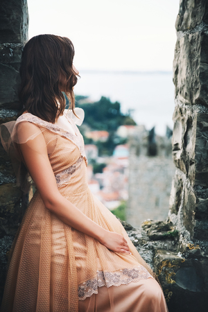 Young beautiful woman in medieval dress on the historical european streets of old town. Bride or young model girl in Piran, Slovenia, Europe. Stock Photo