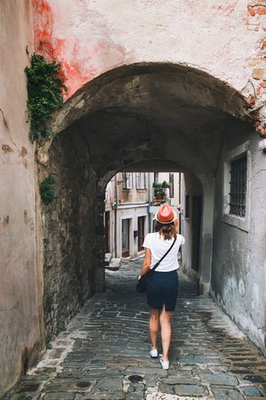 Young woman walks on the historical european streets of old town. Typical medieval italian and istrian streets. Beautiful girl travel Europe. Tourist examines the architecture sights of the city.