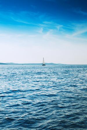 青い海でのセーリング ヨット。青空と山々 を背景に帆船。自然の海の風景。ヨット。コピー スペースと写真。 写真素材