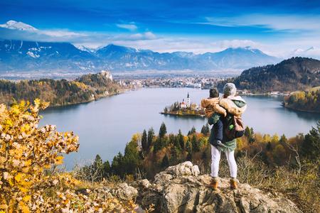 Familie reizen Europa. Moeder met zoon kijkend naar Bled Lake. Herfst of Winter in Slovenië, Europa. Bovenaanzicht op eiland met katholieke kerk in Bled Lake met kasteel en bergen in de achtergrond.