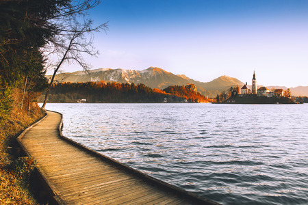 Amazing view on Bled Lake on sunrise with wooden promenade. Island with Catholic Church in Bled Lake with Castle and Mountains. Morning on the lake at dawn. Autumn, Winter in Slovenia, Europe.