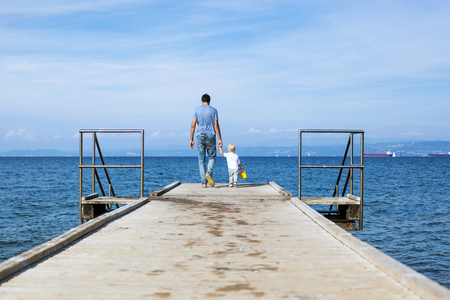 Father with son walking on the sea pier. Family background. Lifestyle concept. Parent and child together.