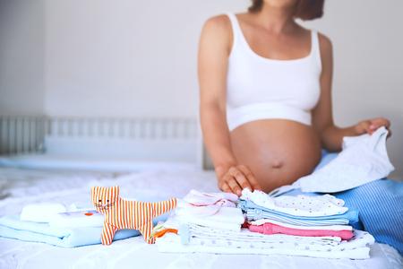Pilha da roupa do bebê, necessidades e mulher gravida na cama no interior home do quarto. Mulher grávida está se preparando para o hospital maternidade, embalagem de coisas de bebê. Gravidez, conceito de nascimento.