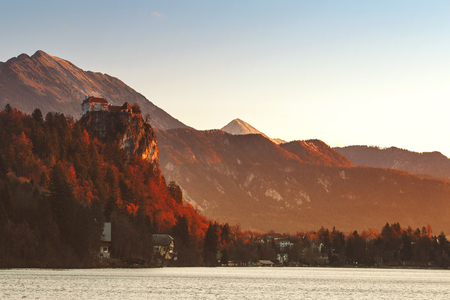 Amazing view on Bled Lake on sunrise. View on Bled Castle and village with Alps on background. December morning on the lake at dawn. Autumn, Winter in Slovenia, Europe.