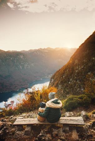 Moeder met zoon die zonsondergang in bergen bekijkt. Herfst op het meer van Bohinj, Slovenië. Vogar-uitkijkpunt. Bovenaanzicht. Vrouw en haar kind op aard. Mooie gelukkige familie brengt tijd door op alpine meer.