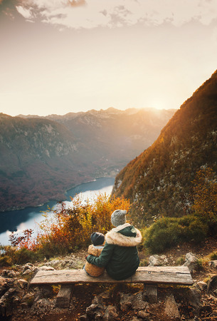 Mother with son looking at sunset in mountains. Autumn on Lake Bohinj, Slovenia. Vogar view point. Top view. Woman and her child on nature. Beautiful happy family spends time on alpine lake.