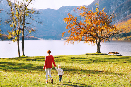 Mother and son walking outdoors. Autumn on Lake Bohinj, Slovenia, Europe. Woman and her child happy on nature. Family spends the fall holidays in a beautiful alpine lake.