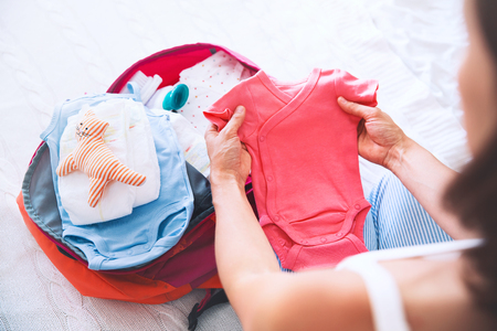 Pregnant woman packing suitcase, bag for maternity hospital at home, getting ready for newborn birth, labor. Pile of baby clothes, necessities and pregnant women at awaiting. Stok Fotoğraf - 83754998