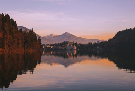 Amazing view on Bled Lake on sunrise. View on Bled village with snowy Alps on background. December morning on the lake at dawn. Autumn, Winter in Slovenia, Europe. Stok Fotoğraf