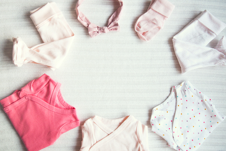 Baby clothes on light pastel fabric background. Gentle, soft and cozy mood. Newborn background with copy space. 스톡 콘텐츠