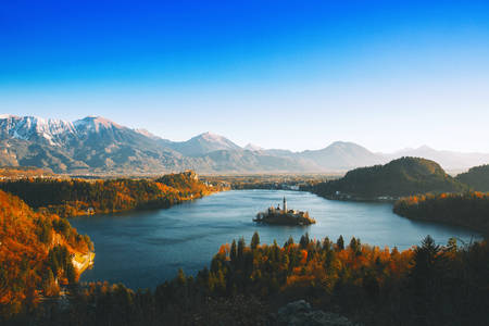 Morning on Bled Lake at dawn. Autumn or Winter in Slovenia, Europe. Top view on Island with Catholic Church in Bled Lake with Castle and Alps in Background.