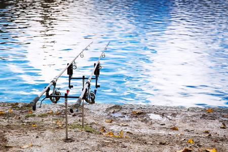 호수 Bled, 슬로베니아의 은행에 낚시 대. 낚시 배경입니다. 부드러운 물 표면의 배경에 두 회전