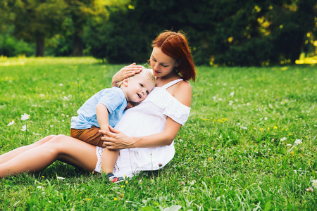 Pregnant woman with toddler kid outdoors. Mother and her son on nature in summer park. Little child boy hugging mother, who pregnant for second time. Pregnancy, new life, family, birth concept. Standard-Bild