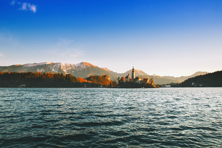Amazing view on Bled Lake on sunrise with Island with Catholic Church, Castle and snowy Alps. Morning on the lake at dawn. Autumn, Winter in Slovenia, Europe.