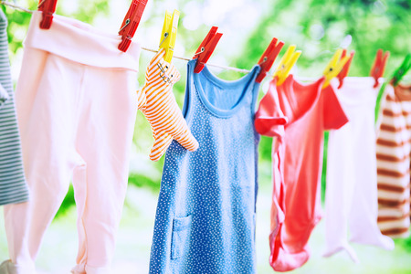 Baby cute clothes hanging on the clothesline outdoor. Child laundry hanging on line in garden on green background. Baby accessories. Imagens