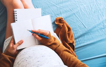 妊娠中の女性はノートと医療のドキュメントを見ています。妊娠、医療、産婦人科、医学の概念。赤ちゃんの母待っています。