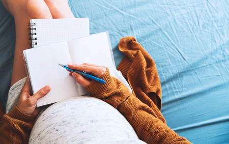 Pregnant woman makes notes and looking at medical documents. Concept of pregnancy, health care, gynecology, medicine. Mother waiting of baby. Standard-Bild