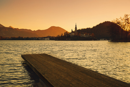 Amazing view on Bled Lake on sunrise with wooden pier. View on Island with Catholic Church. November morning on the lake at dawn. Autumn in Slovenia, Europe. Stok Fotoğraf - 84214259
