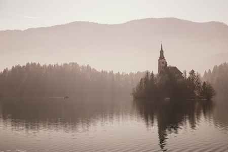 Amazing view on Bled Lake in fog. Mysterious view on Island with Catholic Church in the middle of the lake. Autumn, Winter in Slovenia, Europe.