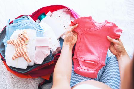 Donna in gravidanza valigia di imballaggio, borsa per ospedale di maternità a casa, prepararsi per la nascita neonato, lavoro. Mucchio di vestiti, necessità e donne in gravidanza in attesa.