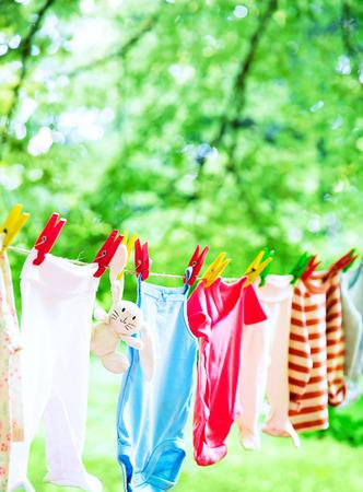 赤ちゃんのかわいい服は物干し屋外にぶら下がっています。緑の背景に庭のラインにぶら下がって子供の洗濯。ベビーアクセサリー。
