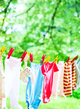 Baby cute clothes hanging on the clothesline outdoor. Child laundry hanging on line in garden on green background. Baby accessories. Stockfoto