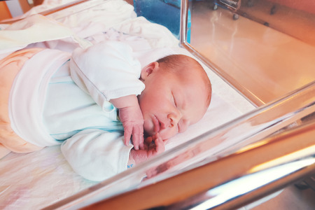 Newborn baby first days of life in delivery room. Infant asleep in hospital after childbirth. 스톡 콘텐츠