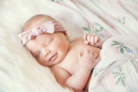Sleeping newborn baby in a wrap on white blanket. Beautiful portrait of little child girl 7 days, one week old. Baby smiling in a dream.