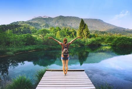 Junge Frau steht auf einer Holzbrücke mit den angehobenen Armen oben auf dem Naturhintergrund. Reise, Freiheit, Lifestyle-Konzept. Slowenien, Europa. Standard-Bild - 91905322